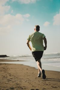 Keeping healthy in the workplace: Man running on the beach